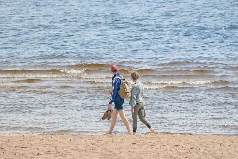 Homme et femme marchant le long du bord de la mer image libre de droits