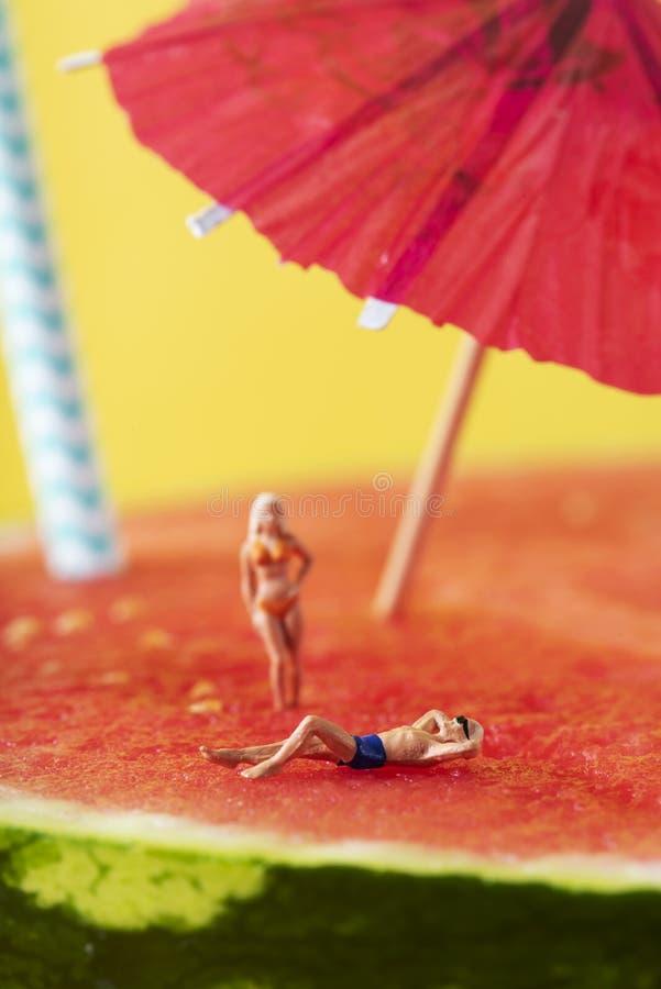 Homme et femme miniatures dans le maillot de bain sur la pastèque photos libres de droits