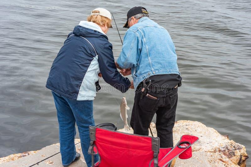 Homme et femme pêchant un poisson photos libres de droits