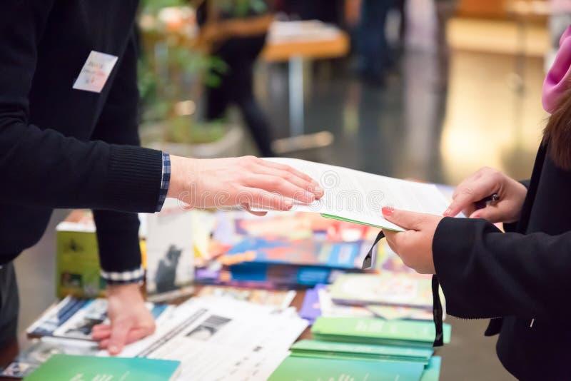 Homme et femme partageant la brochure de l'information au-dessus du support d'exposition photos stock