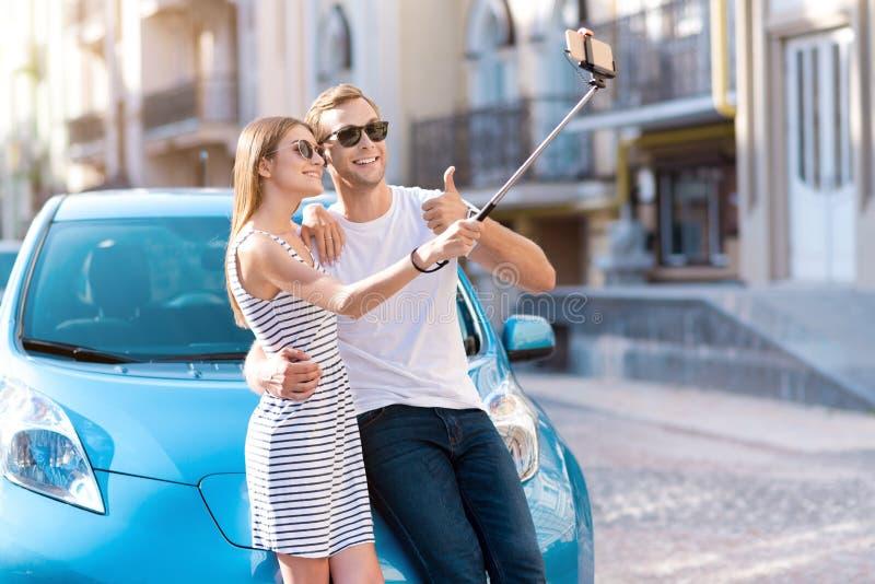 Homme et femme prenant le selfie près de la voiture photo stock