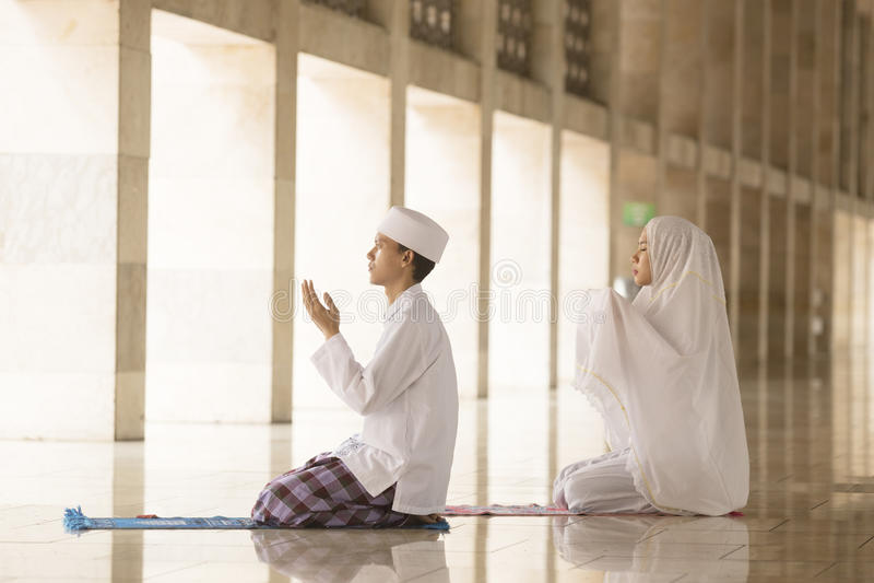 Homme et femme priant dans la mosquée photos stock