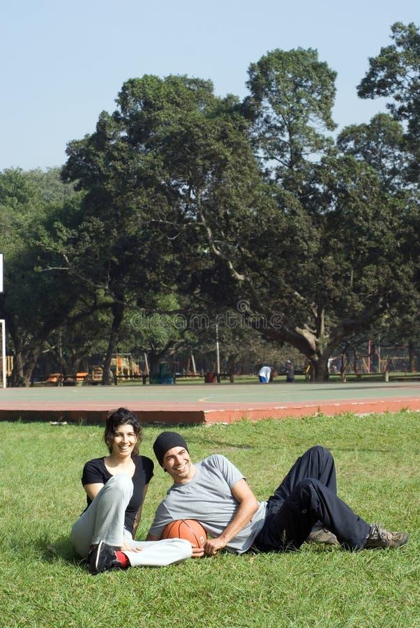Homme et femme s'asseyant en stationnement - verticale photographie stock