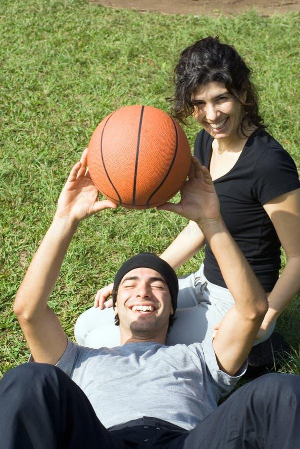 Homme et femme s'asseyant sur l'herbe - verticale photographie stock libre de droits