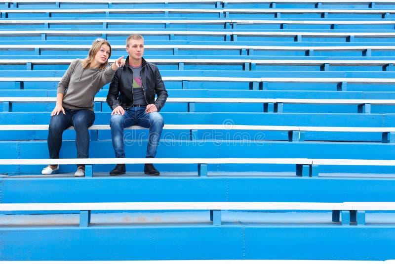Homme et femme s'asseyant sur la tribune photo libre de droits
