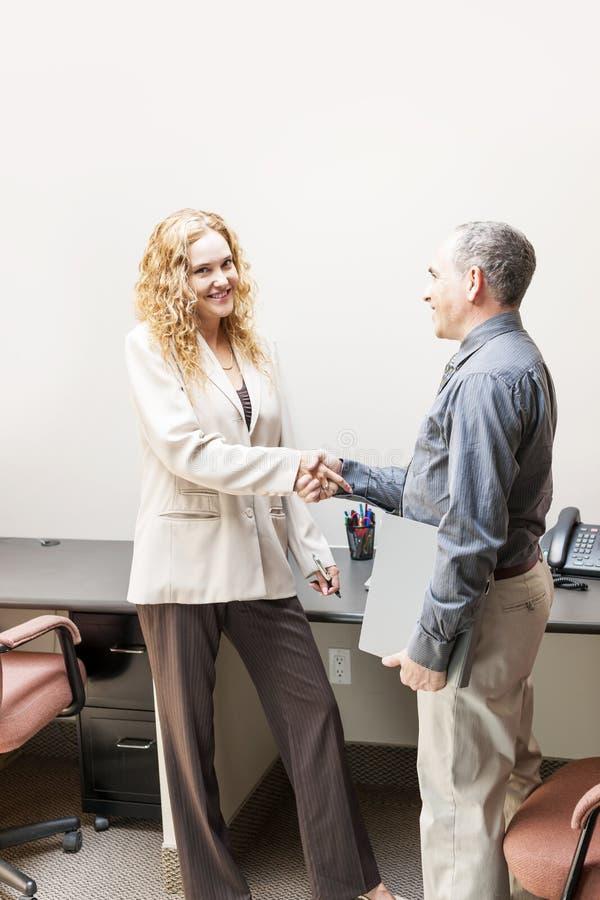 Homme et femme se serrant la main dans le bureau photographie stock