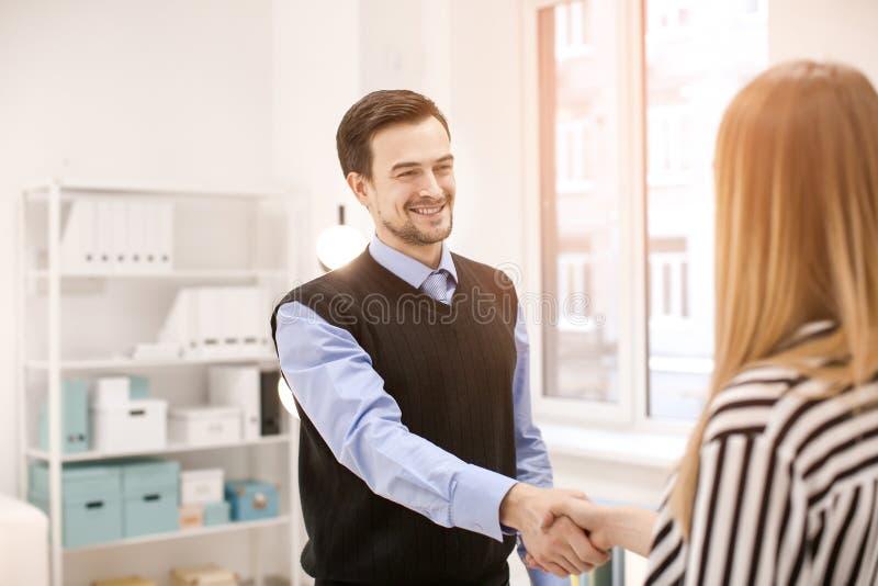 Homme et femme se serrant la main dans le bureau R?union d'affaires r?ussie photographie stock libre de droits