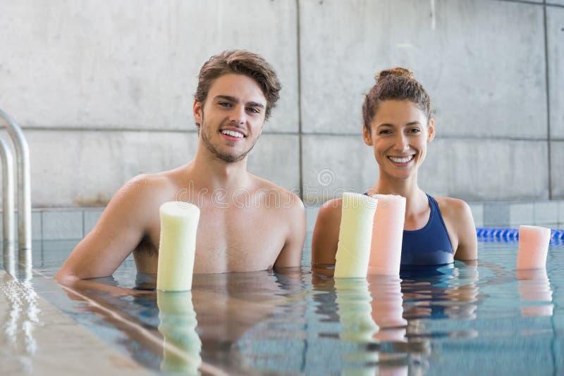 Homme et femme se tenant avec des rouleaux de mousse dans la piscine photos stock