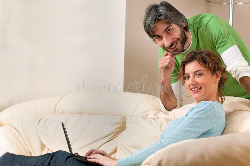 Homme et femme souriant à la maison sur le divan photographie stock libre de droits