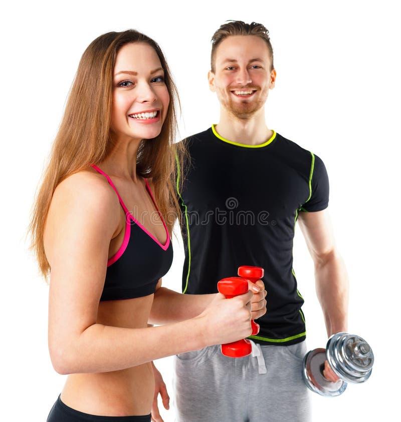 Homme et femme sportifs avec des haltères sur le blanc photo stock
