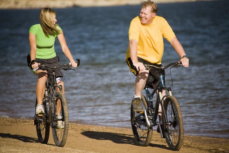 Homme et femme sur des vélos image stock