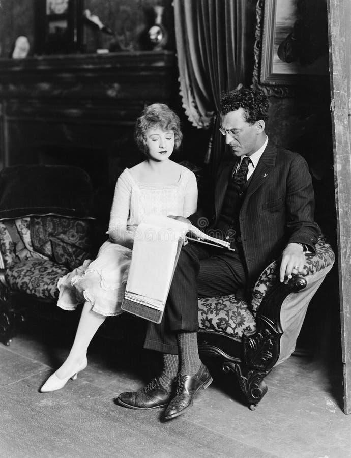 Homme et femme sur le divan avec des écritures photographie stock libre de droits