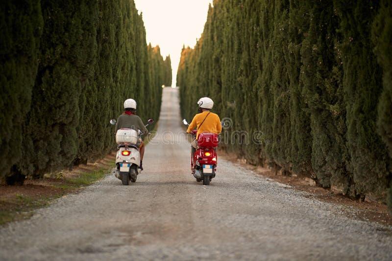 Homme et femme sur le voyage par la route romantique sur le scooter au coucher du soleil Vue arri?re photographie stock