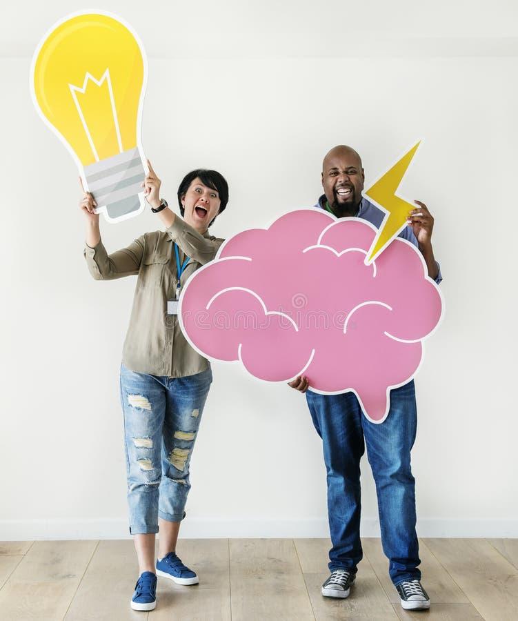 Homme et femme tenant l'ampoule et les icônes roses de nuage respectivement image stock