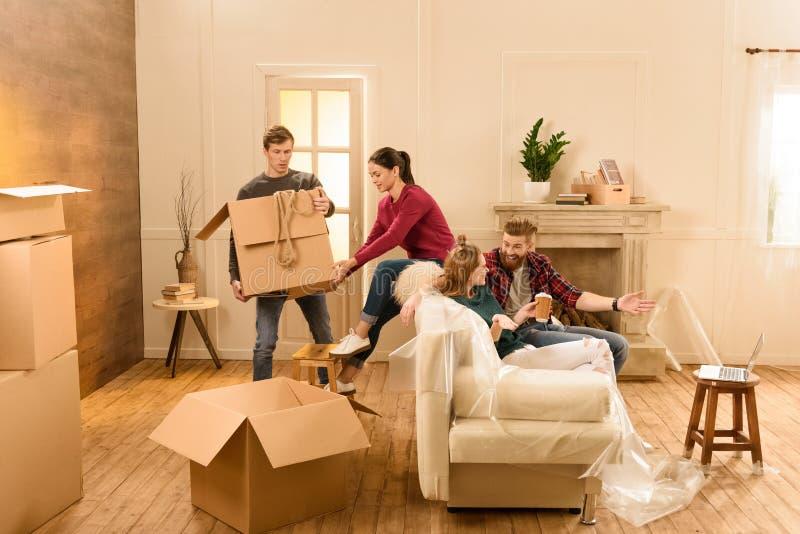Homme et femme tenant la boîte tandis que parler d'amis image stock