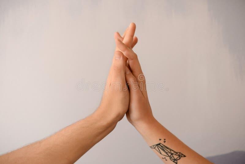 Homme et femme touchant des paumes sur le fond gris image stock