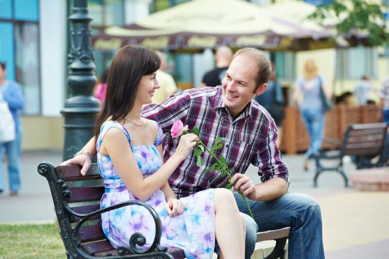 Homme et fille avec la fleur au banc de rue une datte photos stock