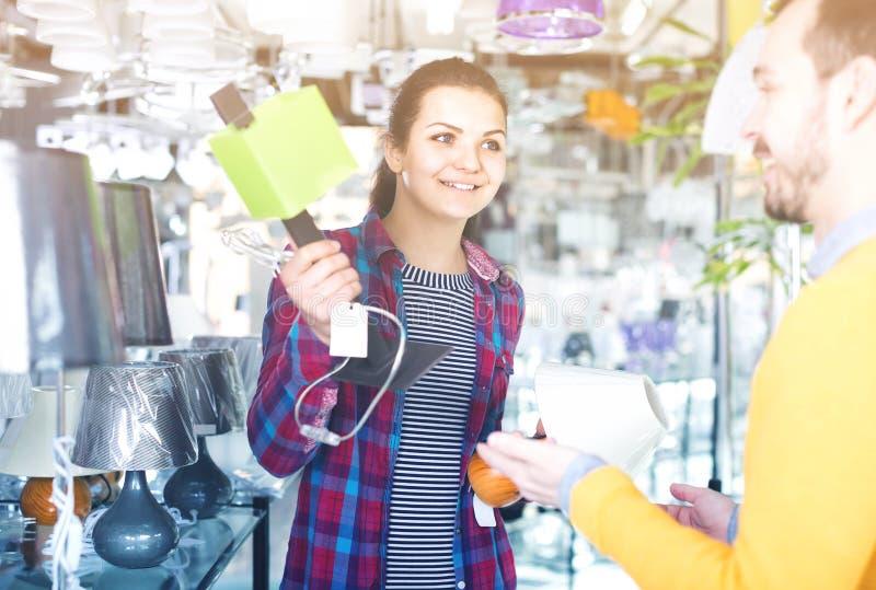 Homme et fille dans une boutique plus légère choisissant la lampe élégante et moderne FO images libres de droits