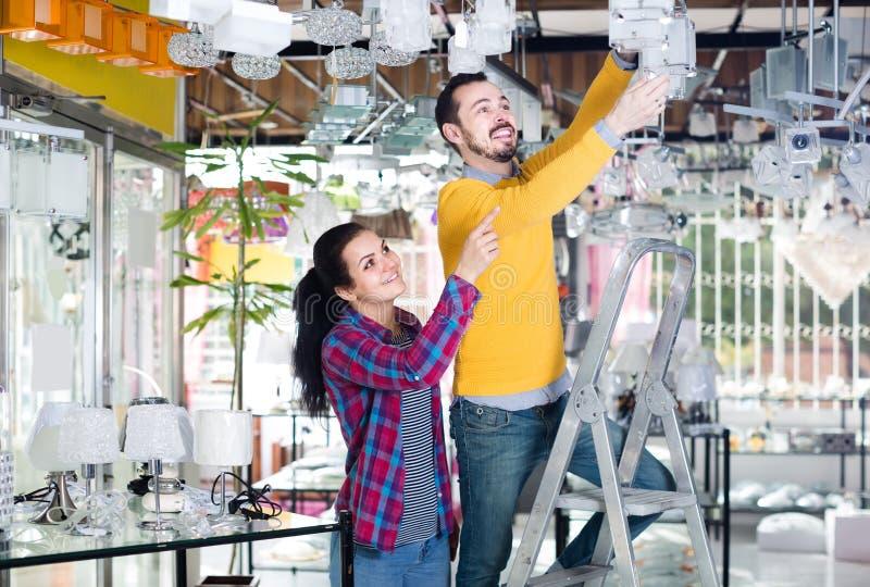 Homme et fille dans une boutique plus légère choisissant le plafond en verre rond moderne photographie stock libre de droits