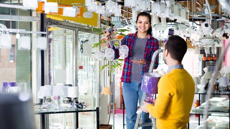 Homme et fille de sourire dans une boutique plus légère choisissant chan de verre élégant photos libres de droits