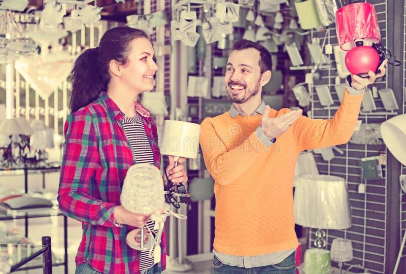 Homme et fille de sourire dans une boutique plus légère discutant l'achat de proche photo libre de droits