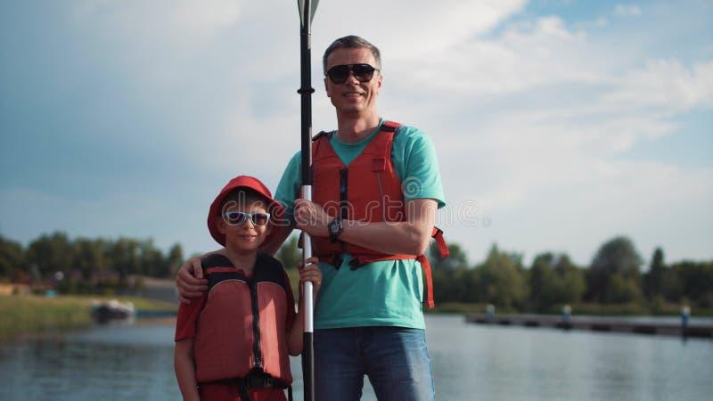 Homme et garçon posant avec l'aviron images libres de droits