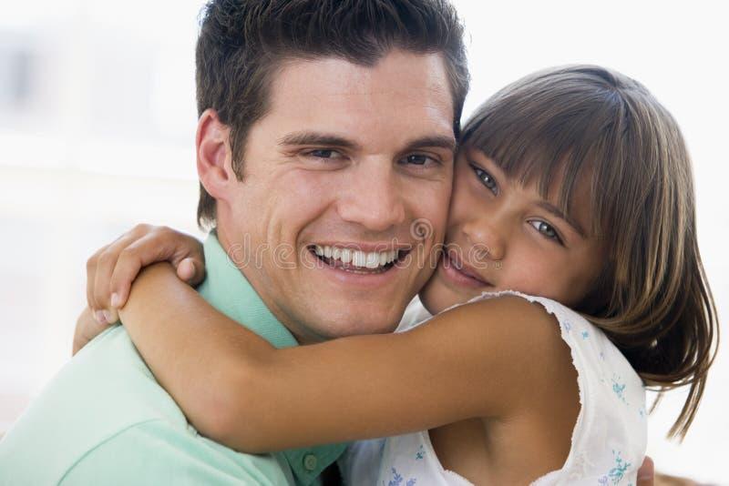 Homme et jeune fille étreignant et souriant photographie stock libre de droits