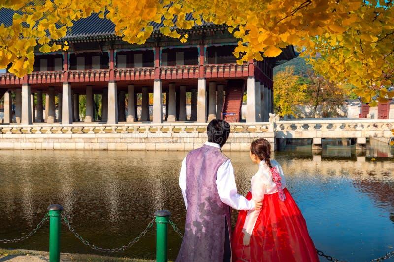 Homme et Madame dans la promenade de robe de hanbok dans le palais de Séoul dans le jardin d'automne de ginkgo photos stock