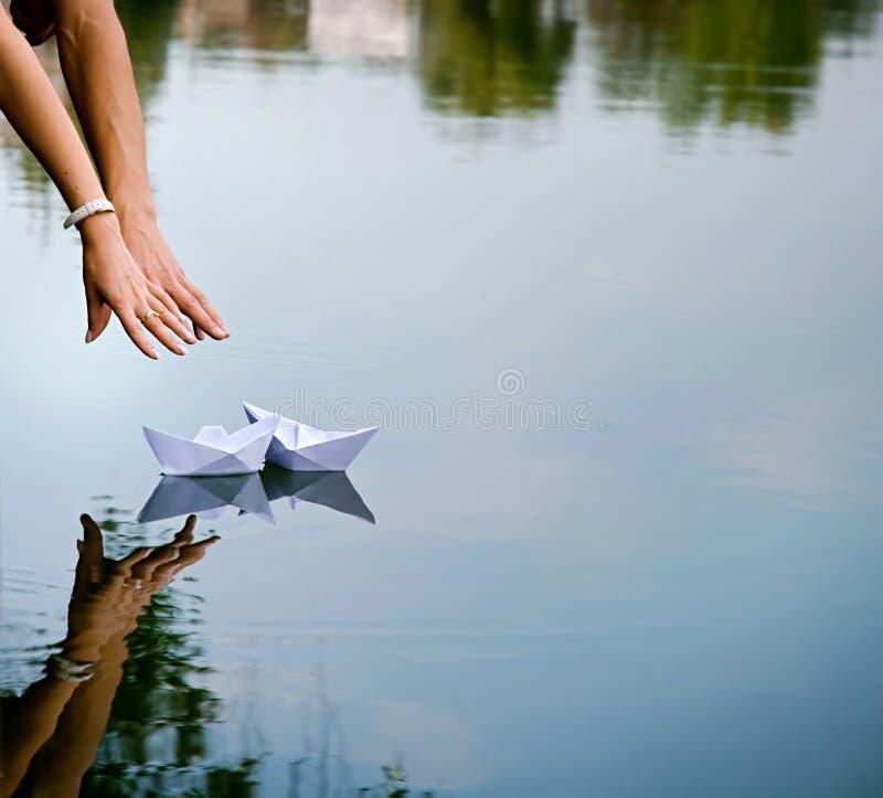 Homme et mains et deux bateaux de papier de la femme photos stock