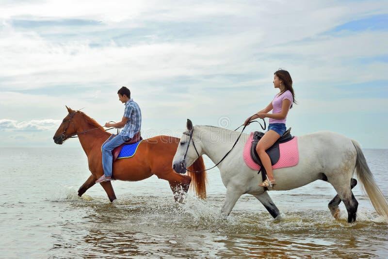 Homme et un femme à cheval photographie stock libre de droits