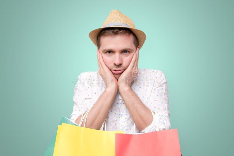 Homme europ?en ennuy? se penchant sur la paume tenir des paquets apr?s l'achat photo stock