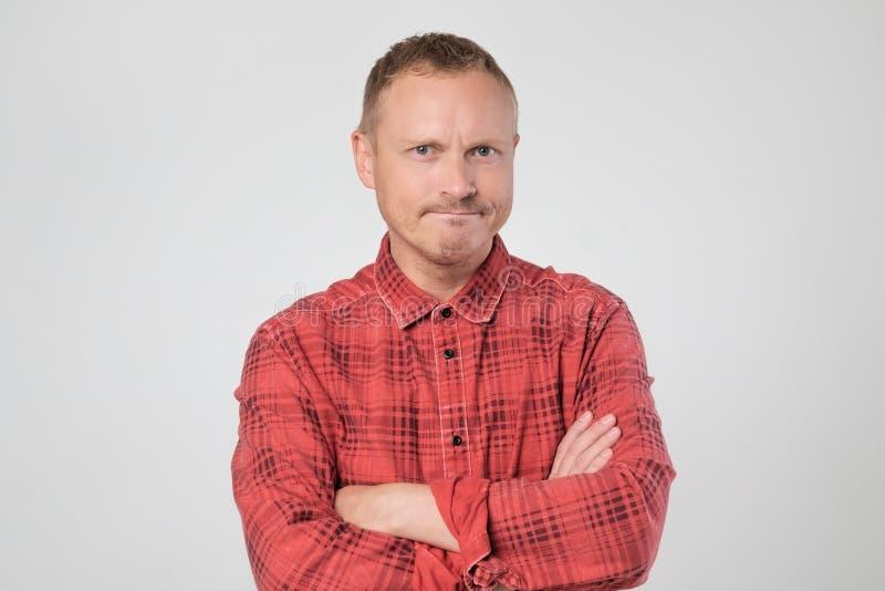 Homme européen mûr grincheux posant dans le studio avec des bras pliés images libres de droits