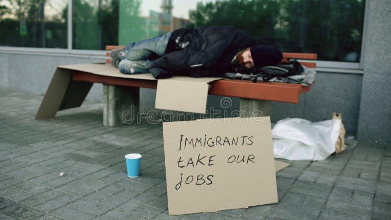 Homme européen sans abri et sans emploi avec le sommeil de signe de carton sur le banc à la rue de ville en raison de la crise d' image libre de droits