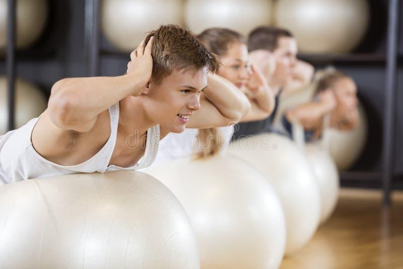 Homme exécutant l'exercice arrière d'extension avec des amis sur des boules photos stock