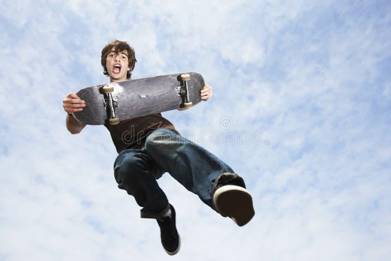 Homme exécutant le tour sur la planche à roulettes photo libre de droits