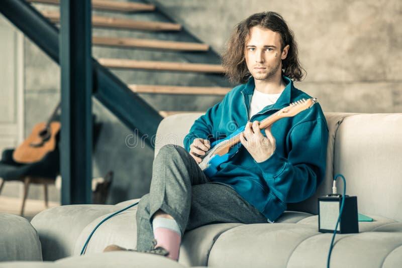 Homme extraordinaire bel utilisant l'équipement élégant tout en formant ses qualifications de guitare photo libre de droits