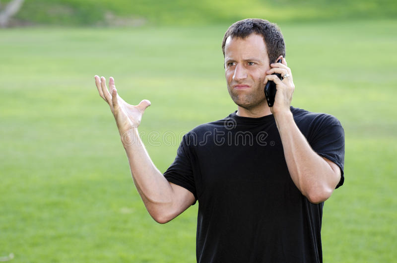 Homme fâché à son téléphone portable images stock