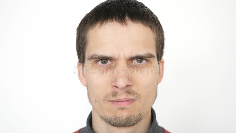 Homme fâché avec les yeux mauvais, expression dramatique sérieuse Plan rapproch? sur un fond blanc photo libre de droits