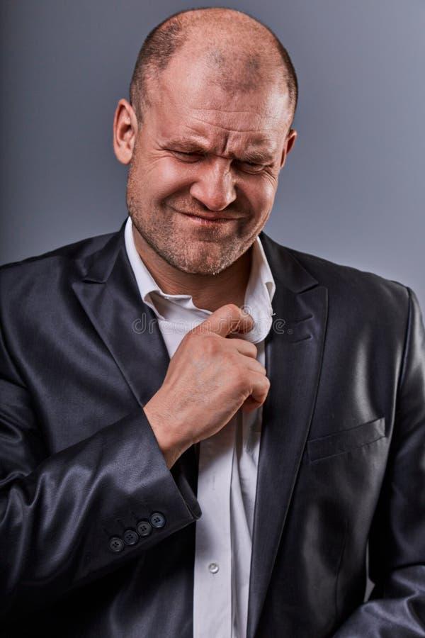Homme f?ch? chauve soumis ? une contrainte malheureux d'affaires tirant le collier de chemise avec des ?motions tr?s mauvaises da photos libres de droits