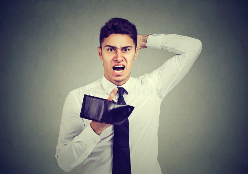 Homme fâché choqué et frustrant, tenant un portefeuille vide image stock