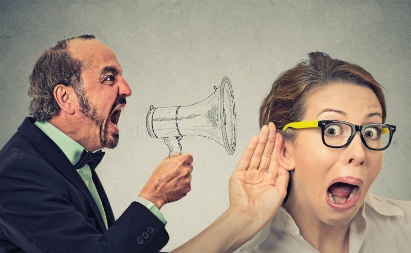 Homme fâché criant dans l'écoute fouineuse curieuse de femme de mégaphone photos libres de droits