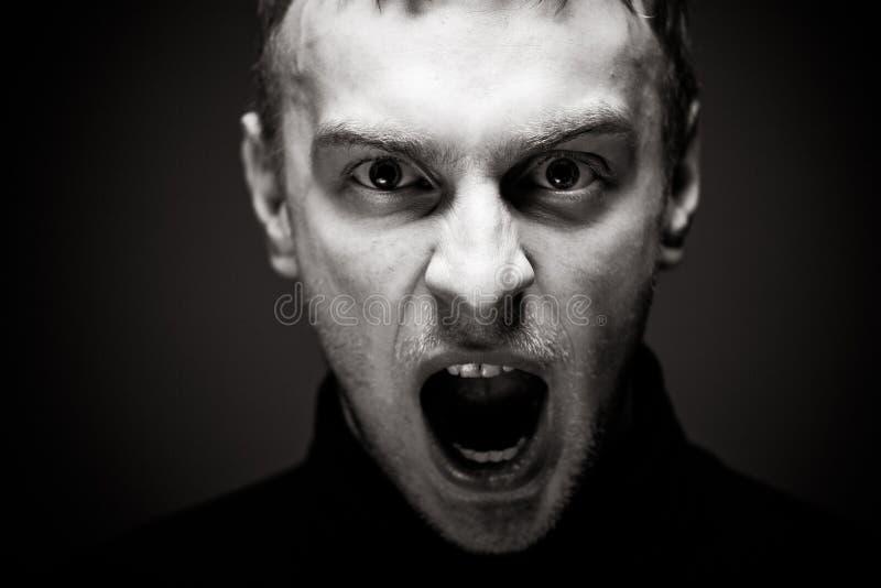 Homme fâché criant Un homme dans une chemise noire image stock