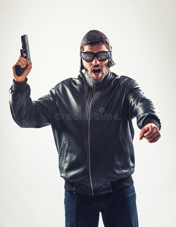 Homme fâché déguisé tenant une arme à feu menaçant image stock