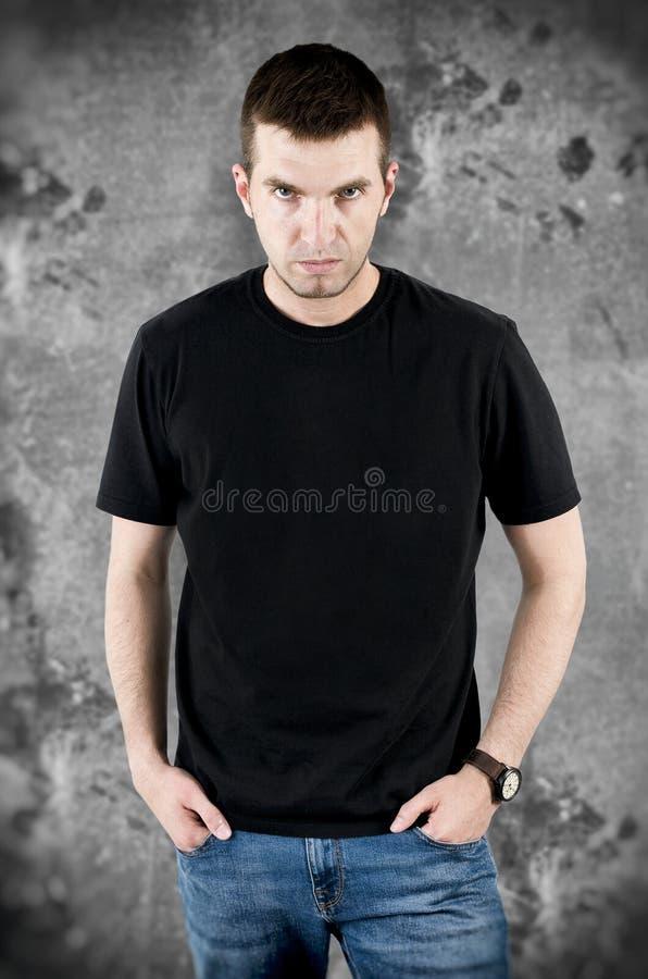 Homme fâché dans le T-shirt noir sur le fond grunge images libres de droits