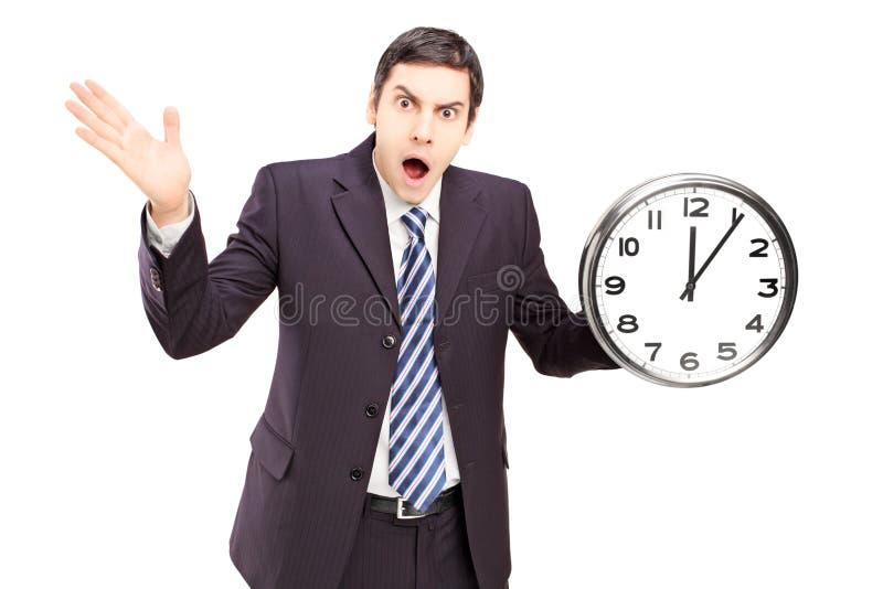 Homme Fâché Dans Un Costume Tenant Une Horloge Et Faire Des Gestes Image stock