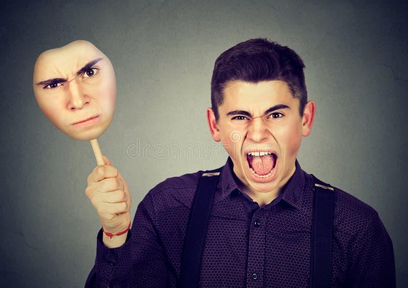 Homme fâché enlevant le masque avec l'expression grincheuse de visage photo stock