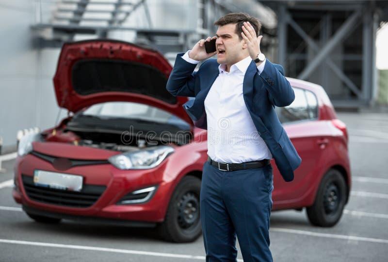 Homme fâché parlant par le téléphone en raison de la voiture décomposée image stock