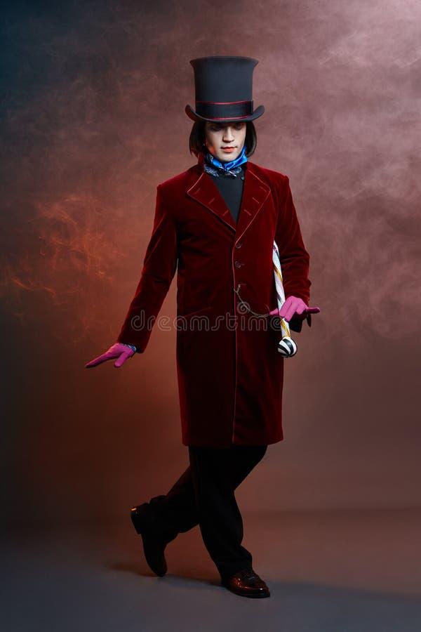 Homme fabuleux de cirque dans un chapeau et un costume rouge posant dans la fumée sur un fond foncé coloré Un clown à une partie, photo libre de droits
