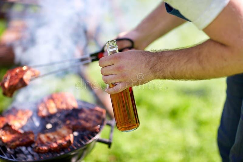Homme faisant cuire la viande sur le gril de barbecue à la partie d'été image stock
