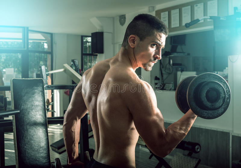 Homme faisant des boucles de biceps photographie stock